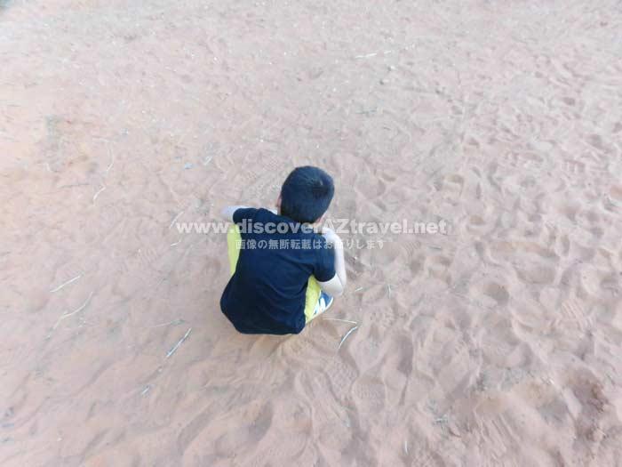 モニュメントバレーの砂で遊ぶ子ども